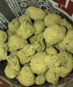 "Moon Rock, also known as ""Kurupt's Moonrock,"" is an infamous take on the classic Girl Scout Cookies strain, where the nugs are dipped in hash oil and then rolled in kief. This process supercharges the effects of Moon Rock, giving it a THC level of about 21-26% in total, making it way too strong for inexperienced users. The high hits you hard immediately after you toke, knocking you hard in the head with a cerebral rush that launches your mind into hazy bliss before leaving you completely stoned in mind and body. You'll be utterly relaxed but totally euphoric as you slip away into a heavy couch-lock and sedation that can easily cause users to fall into a deep and peaceful sleep. Because of these effects and its insanely high THC level, Moon Rock is said to be perfect for treating insomnia, appetite loss, chronic pain, muscle spasms, and cramps. This bud has a unique flavor of earthy nutty hash that has a subtle sweetness to it from the hash oil. The aroma is surprisingly mellow, with a spicy dank overtone that's accented by sweet earth. Moon Rock buds are round and lumpy, coated in bright kief and dripping with hash oil."